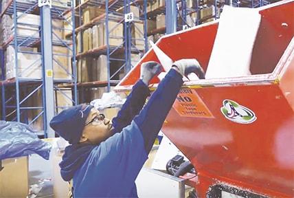 Man shredding Styrofoam for recycling at AFW warehouse
